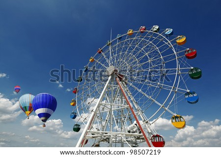 A giant colorful ferris wheel in an amusement park with colorful hot air balloons floating in the horizon on a blue cloudy day. - stock photo