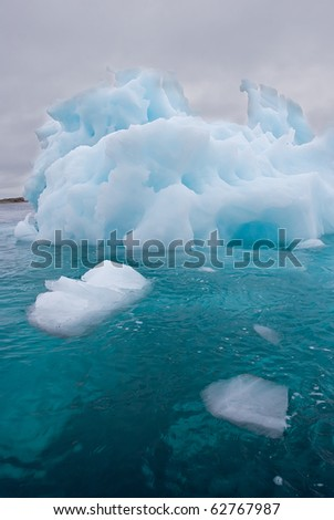a giant iceberg floating under a stormy sky