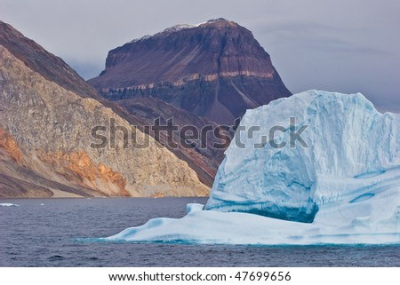 a giant iceberg floats on the sea in greenland