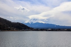 A giant Mt. Fuji stands beneath the blue sky surrounded by clouds. The front is a vast lake Kawaguchiko.