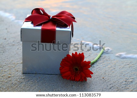A gift box and a daisy flower put on the beach.