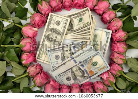 A gift for the holiday laid out around pink beautiful roses and flowers and hundred dollar bills.
