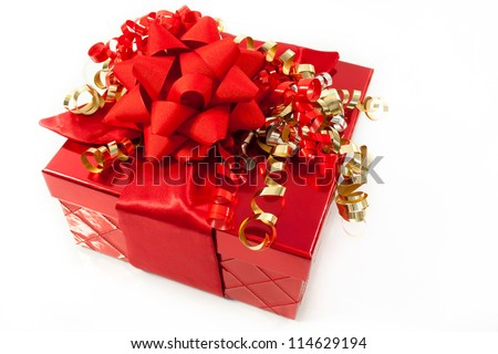 A gift in a red gift box is trimmed with a big red bow and red and gold curly ribbons.