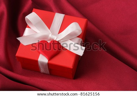 A gift with a red ribbon and heart on red silk