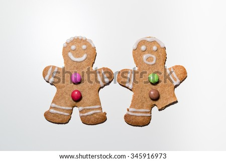 A gingerbread couple, one missing a leg #345916973
