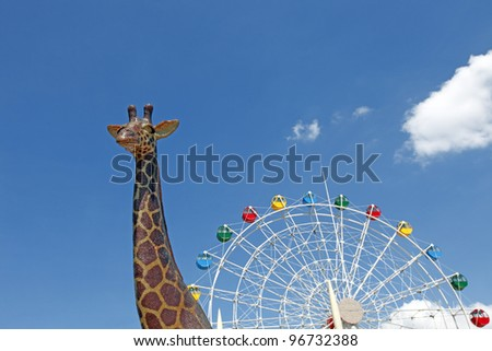 A giraffe with a ferris wheel in the background looking like a giant magical snail, against a blue sky with clouds.