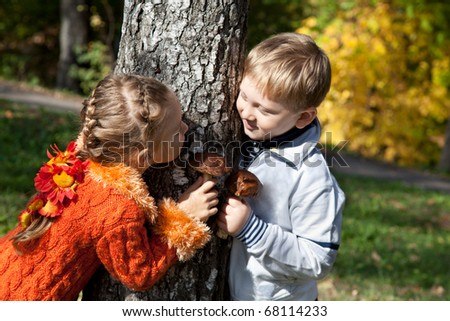 a girl and a boy are playing hide-and-seek in an autumn park