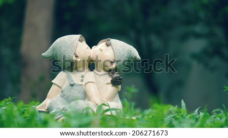 A girl and a boy dolls, kissing each other, sitting on the green grass meadow (love concept)