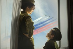 A girl and a boy in a Soviet military uniform are standing at window. Concept of cancelled parade,  which dedicated to the 75th anniversary of Victory in the great Patriotic war in Moscow.