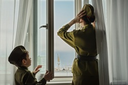 A girl and a boy in a Soviet military uniform are standing at window. The girl adjusts her hat. Consept of parade,  wich dedicated to the 75th anniversary of Victory in the great Patriotic war