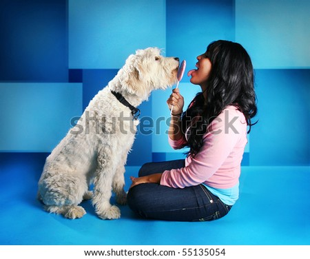 a girl and a dog sharing a sucker