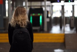 a girl at the entrance to the terminal waiting for a check