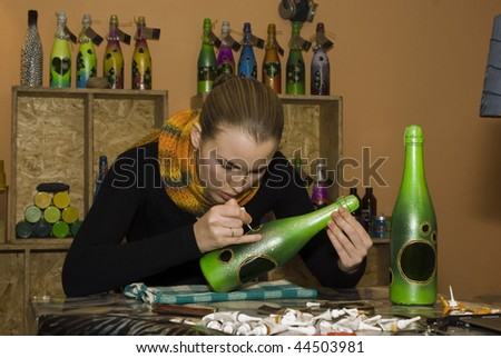 A girl at work in the workshop on hand-made decorative items - stock photo