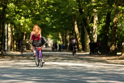 A girl biking on a bunny day in the Amsterdam Vondelpark  in the Netherlands.