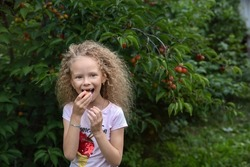 A girl bites a plum ion the garden.Hairstyle after curls
