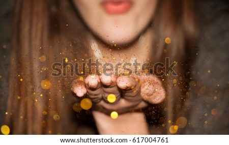 A girl blowing millions of pieces of gold glitter from her hand