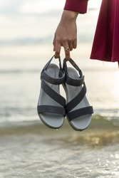 A girl carrying her sandals to avoid getting wet while playing on the beach