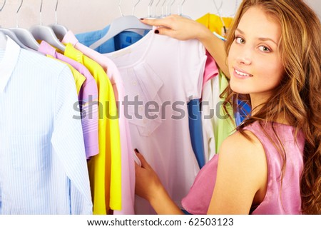 A girl choosing t-shirt in the shop