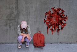 A girl crouches with her head bowed in front of a concrete wall on which graffiti from a coronavirus can be seen
