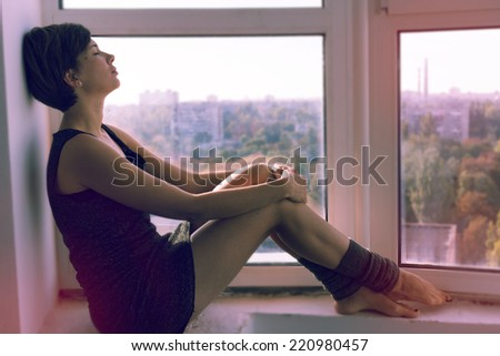 A girl day dreaming near the window. Image in retro style.