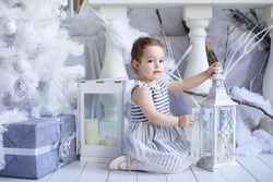 a girl dressed in a dress sitting in a room with Christmas decoration