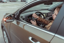 A girl driving a car, looks in a side view mirror, parking at shopping center, turning at an intersection, turning on a turn signal on a car. Left turn. Woman in a leather jacket.