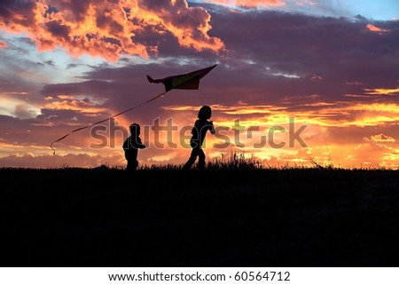 A girl flies a kite at sunset while her brother runs after.