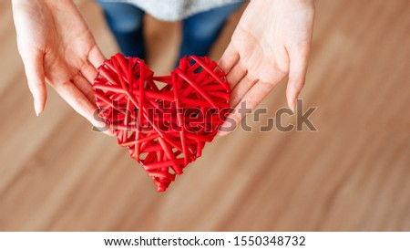 A girl gives a heart of red rods on Valentine's day.