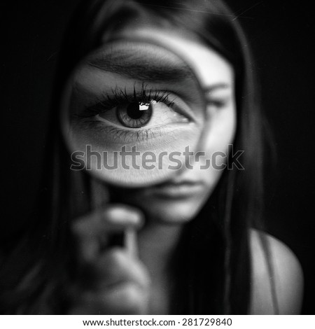 Stock Photo A girl holding a magnifying glass on a dark background, scary big eyes
