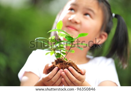 A girl holding a young plant in her hands with a hope of good environment.