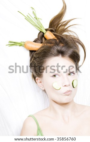 a girl holds a carrot in teeth