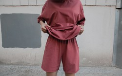 A girl holds a T-shirt from an oversized suit against the wall. Oversized suit. Minimalistic clothing on the model girl. Coral-colored suit. Fashion concept.oversized wear and clothes