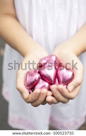 a girl holds pink foiled chocolate hearts in hands