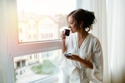 A girl in a bathrobe drinking coffee in the morning on the windowsill.