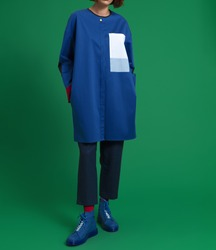 A girl in a beautiful, fashionable, luxurious blue shirt with a white coat pocket, dark trousers, blue shoes, red socks on a green background