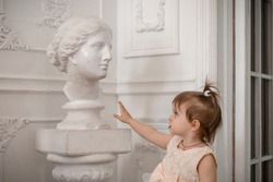 A girl in a beige dress stands in a white room next to a woman's bust