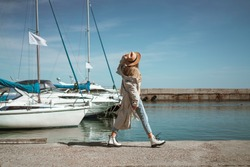 a girl in a beige trench coat and hat walks through the yacht club