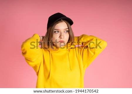 a girl in a black cap and yellow hoodie wears a hood, she has a bauble in LGBT colors on her arm, a pink background behind her