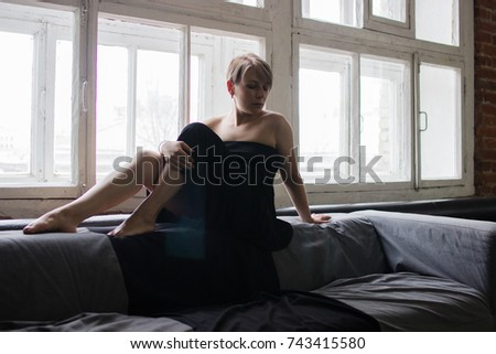 A girl in a black dress is sitting on the sofa near the window. Blond hair, short haircut, does not look at the camera #743415580