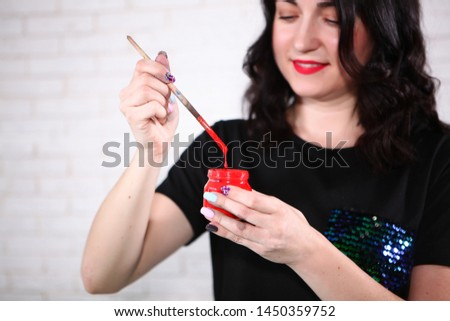 A girl in a black T-shirt is holding a can of paint and a brush. Photo without a face. The concept of hobbies and hobbies. Photos in the interior.