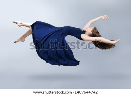 A girl in a blue dress is floating in the air. Dress and hair fluttering in the wind. Flight. Fantasy. Insulation on light grey background. Studio photo