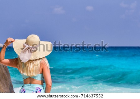 A girl in a blue summer dress with a hat on his head, standing on the white sand. Similan Islands #714637552