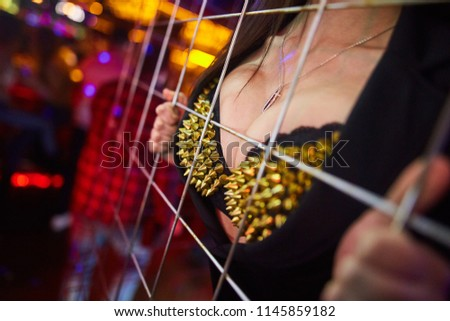 Stock Photo a girl in a bra with yellow metal spikes holds onto a metal grate and presses her breast against it. close-up. background blur.
