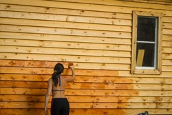 A Girl in a Brassiere paints a wooden wall of orange paint. Idea of repair.