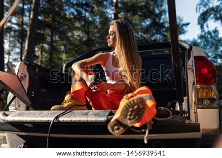 A girl in a building uniform sits in the back of a car with her eyes closed. Female labor. Female builder