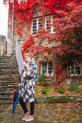 a girl in a coat walks in Monschau with a bright umbrella