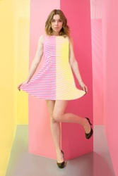 a girl in a dress striped in halves pink and yellow. stands in full growth playfully makes a curtsey. art portrait symmetrical pulls the edge of the dress