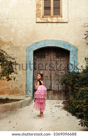 a girl in a fairy dress of a princess with a crown turns around walkng to the door of an ancient castle house