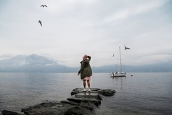 A girl in a green jacket and a pink hat stands with her back on the lake and enjoys the view. Spectacular view of Lake Como. Cloudy and rainy weather, seagulls fly in the sky