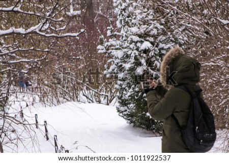 A girl in a green winter jacket with a hood and a black backpack behind her back, takes photos in a snow-covered park. The foreground is in focus. The foreground is blurred. #1011922537